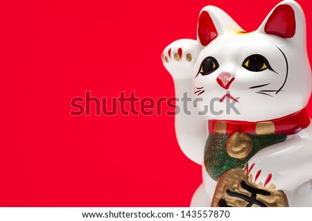 close-up of lucky cat on red background - stock photo