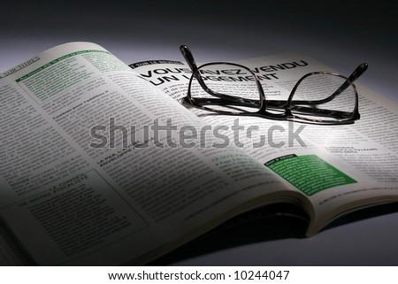 close up of magazine and glasses on the table - stock photo