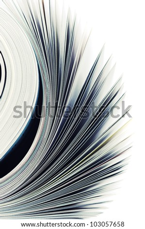 Close-up of magazine pages on white background. Shallow DOF, focus on edges.