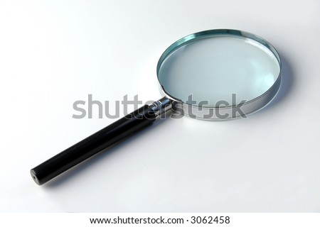 Close up of magnifying glass over a light background