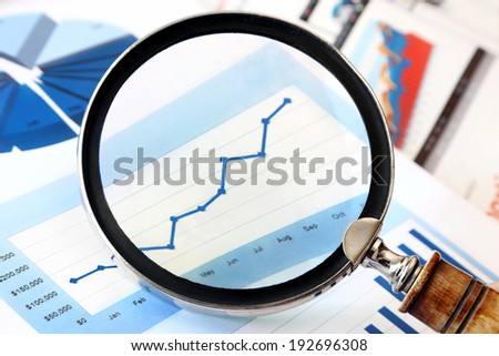 Close-up of magnifying glass over financial Chart  - stock photo