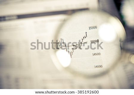 Close-up of magnifying glass over financial graph.  - stock photo