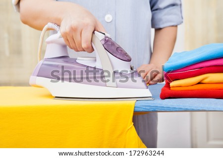 Close-up Of Maid Ironing Clothes On Ironing Board - stock photo