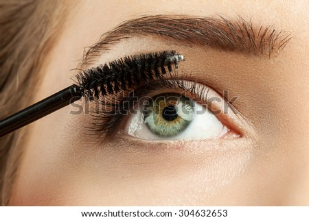Close-up of make-up green eye with long lashes with black mascara