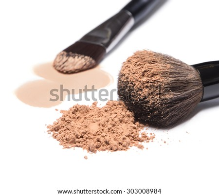 Close-up of makeup brushes with loose cosmetic powder and smeared liquid foundation on white background. Focus on the foreground