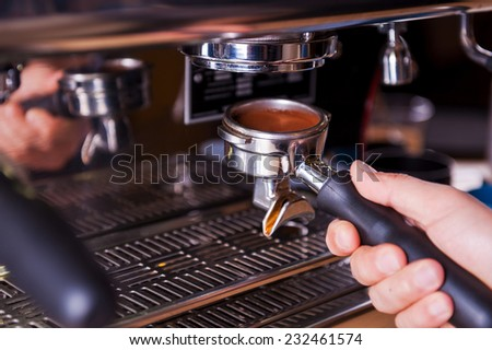 Close-up of making coffee. Close-up image of male barista preparing fresh coffee  - stock photo