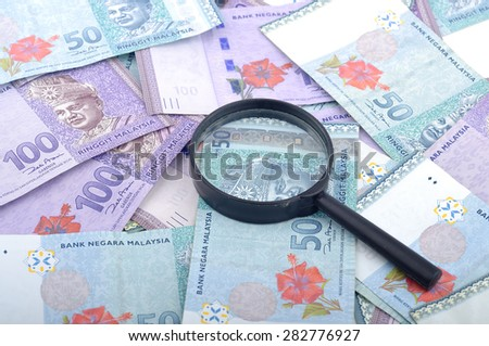 Close Up of Malaysia Bank Notes With Magnifying Glass, Finance Concept Selective Focus