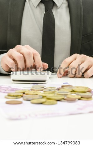 Close up of male accountant in suit calculating expenses. With Euro money on his desk.
