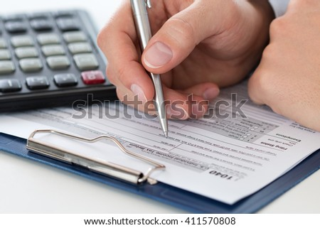Close up of male accountant making calculations. Man writing something sitting at his office. Filling individual income tax return form 1040, making financial report, home finances or economy concept