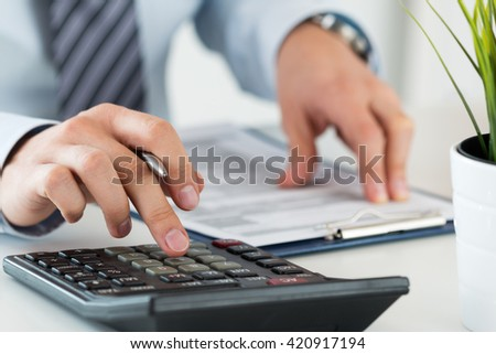Close up of male accountant or banker calculating or checking balance. Bookkeeper or financial inspector making financial report. Home finances, investment, economy, saving money or insurance concept - stock photo
