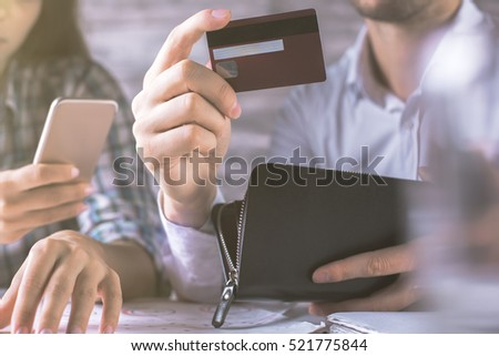 Close up of male and female hands holding purse, credit card and smartphone. Online payment concept