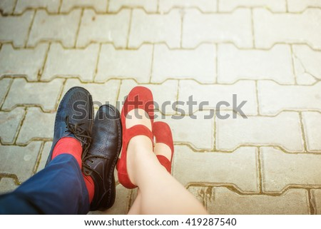 close-up of male and female legs in shoes on the pavement. relax and enjoy the concept - stock photo