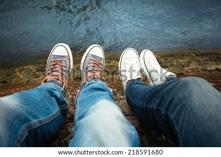 Close up of male and female's feet relaxing by the river - stock photo