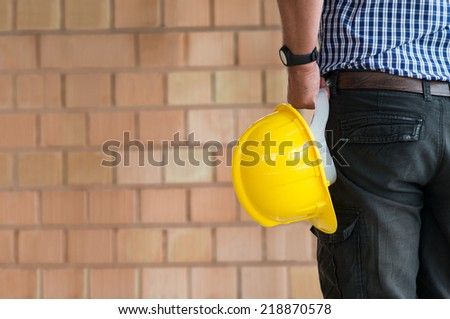 Close up Of Male Architect Holding Yellow Helmet At Construction Site - stock photo