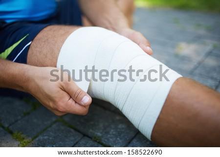 Close-up of male bandaging his leg - stock photo