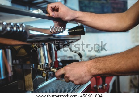 Close-up of male barista using espresso machine at coffee house
