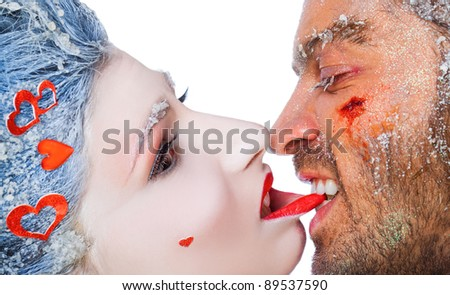 Close-up of male biting woman's lip, both faces covered with frost