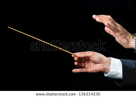 Close up of male conductors hands ready to direct. - stock photo