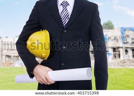 Close up of male contractor wearing formal suit and holding a blueprint on the residential construction - stock photo