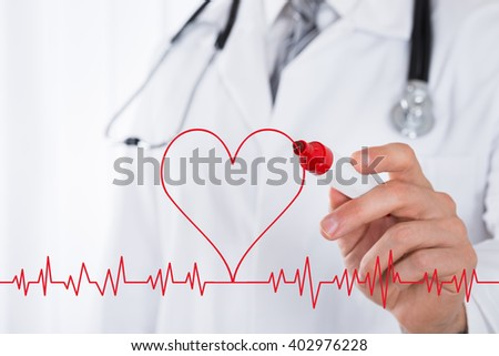 Close-up Of Male Doctor Hand Drawing A Heart Symbol Near Electrocardiogram With Red Marker - stock photo
