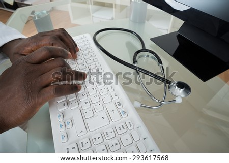 Close-up Of Male Doctor Hands Typing On Computer Keyboard At Desk - stock photo