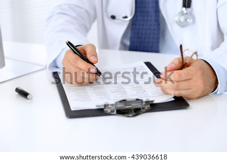 Close up of male doctor is sitting at the table and filling up medical history form - stock photo