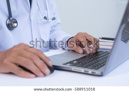 Close up of male doctor working on laptop computer, electronic health records system EHRs, electronic medical records system EMRs, telemedicine concept.