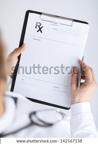 close up of male doctor writing prescription paper - stock photo