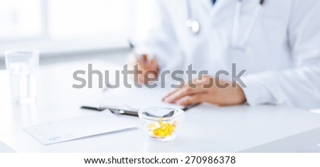 close up of male doctor writing prescription paper and capsules - stock photo