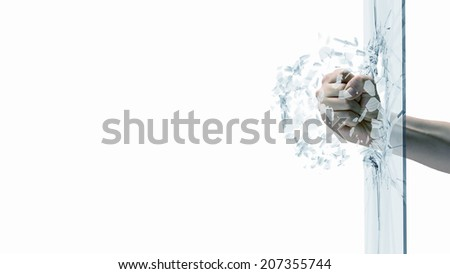 Close up of male fist breaking glass with punch - stock photo