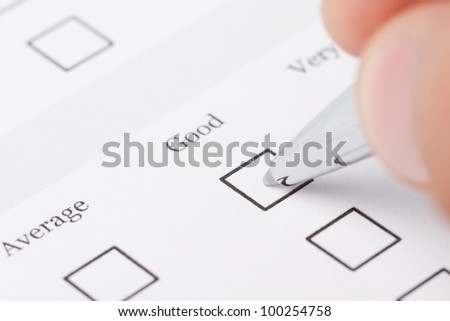 Close up of male hand filling out the questionnaire - stock photo