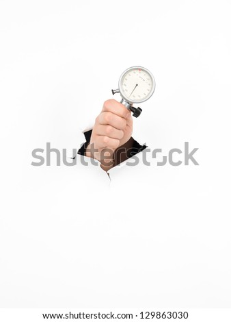 close-up of male hand holding an indicator clock through a torn white paper, isolated - stock photo