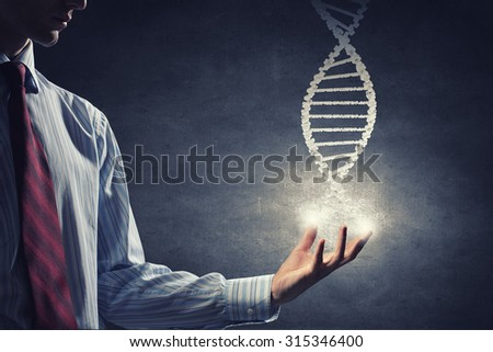 Close up of male hand holding DNA molecule in palm - stock photo