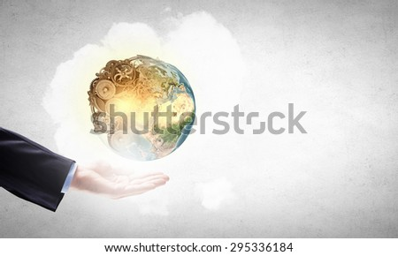Close up of male hand holding our Earth planet. Elements of this image are furnished by NASA