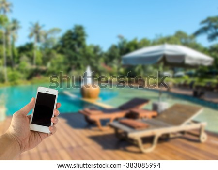Close up of Male Hand Holding Smart Mobile Phone with Blank Screen on The Blur Swimming Pool with Various Tree in Luxury Hotel used as Template to input Text or Photo, Business Concept - stock photo