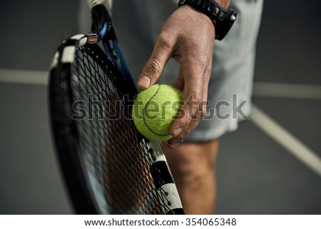 Close-up of male hand holding tennis ball and racket. Professional tennis player starting set. - stock photo