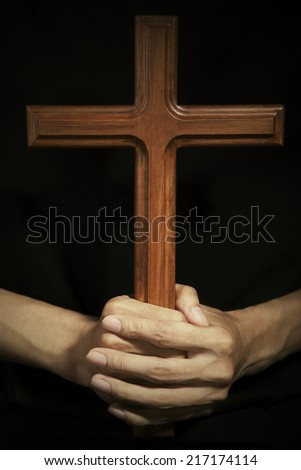 Close-up of male hand holding wooden cross - stock photo