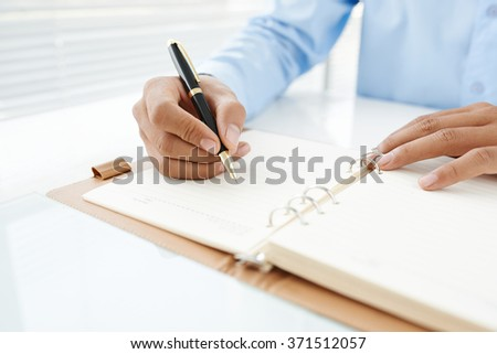 Close-up of male hand making notes in organizer