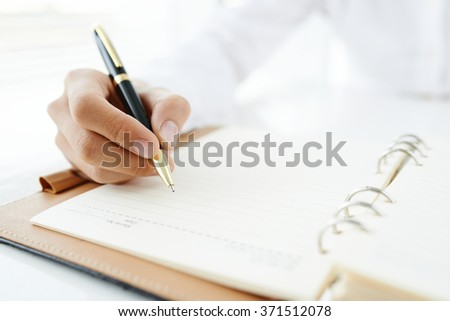 Close-up of male hand making notes with a pen - stock photo