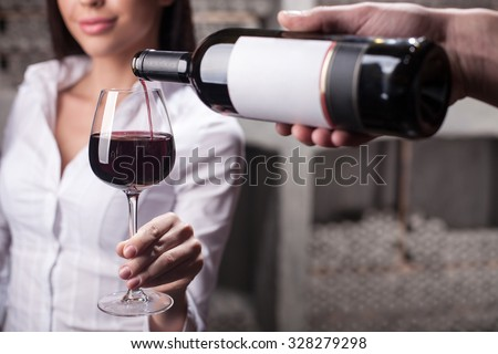 Close up of male hand of sommelier serving woman. The man is holding a bottle and pouring wine into glass. The woman is holding wineglass and smiling. She is standing in cellar - stock photo