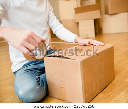 Close up of male hand packing cardboard box - stock photo