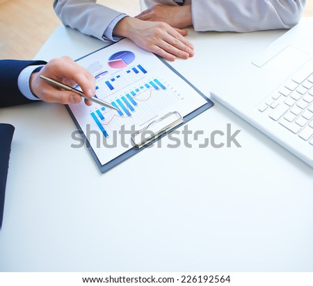 Close-up of male hand pointing at business document while explaining it to businesswoman - stock photo