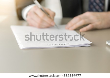 Close up of male hand putting signature in contract making it valid, considering hiring specific wholesaler to provide product, names of people who are authorized to agreement. Focus on word Contract