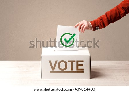 Close up of male hand putting vote into a ballot box, on grunge background - stock photo