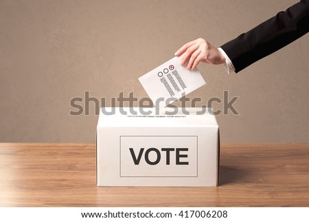 Close up of male hand putting vote into a ballot box, on grungy background - stock photo