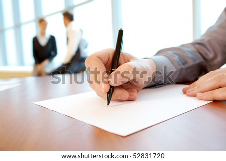 Close-up of male hand with pen over paper during conference