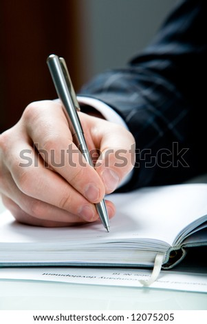 Close-up of male hand with pen ready for writing
