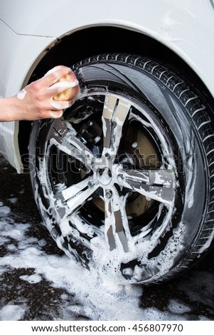 close up of male hand with sponge washing car wheel - stock photo