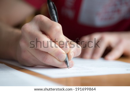 Close-up of male hand writing - stock photo