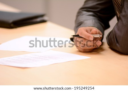 Close-up of male hands. Decision of signing the contract - stock photo